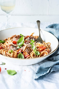 Klopsik spaghetti z sosem pomidorowym marinara polany parmezanem i bazylią fotografia kulinarna