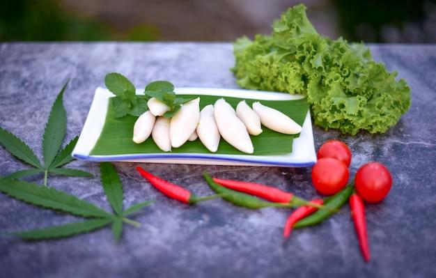 Klopsiki gotowane na parze, liście konopi i warzywa na ciemnym tle