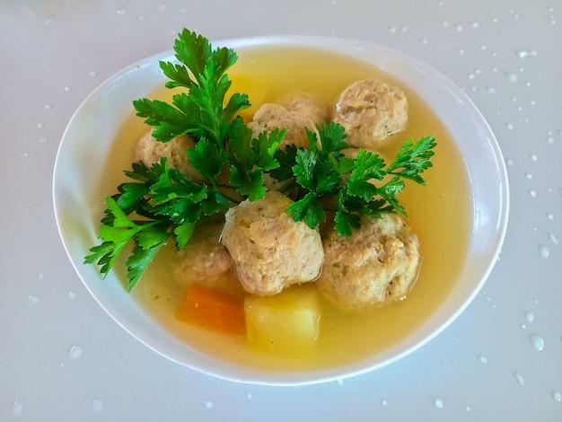 Klopsiki i ziemniaki w zupie jarzynowej w białym talerzu.