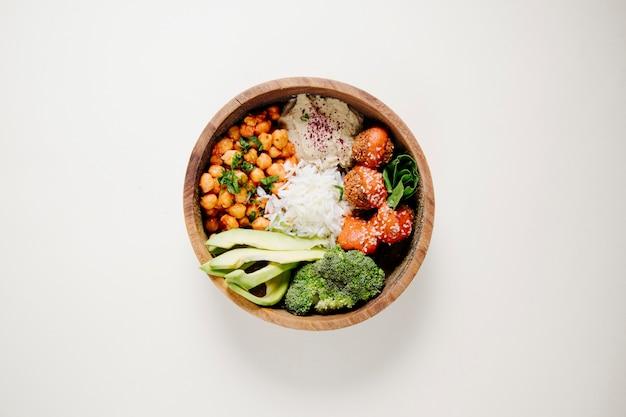 Klopsiki, ryż, fasola i brokuły w drewnianej misce.