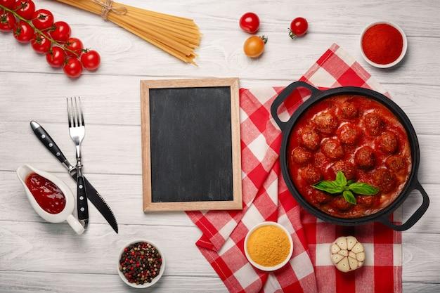 Klopsiki w pomidorowym kumberlandzie z pikantność w smaży niecce i czereśniowymi pomidorami na białej drewnianej desce