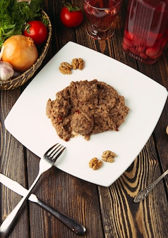 Klopsiki w sosie dipowym z orzecha włoskiego, podawane w białym talerzu.