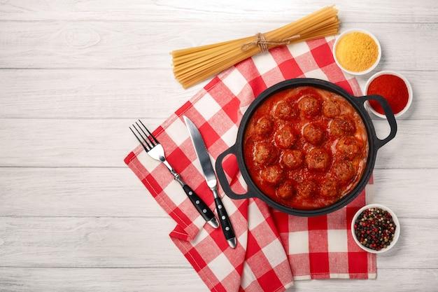 Klopsiki w sosie pomidorowym z przyprawami na patelni na białej desce