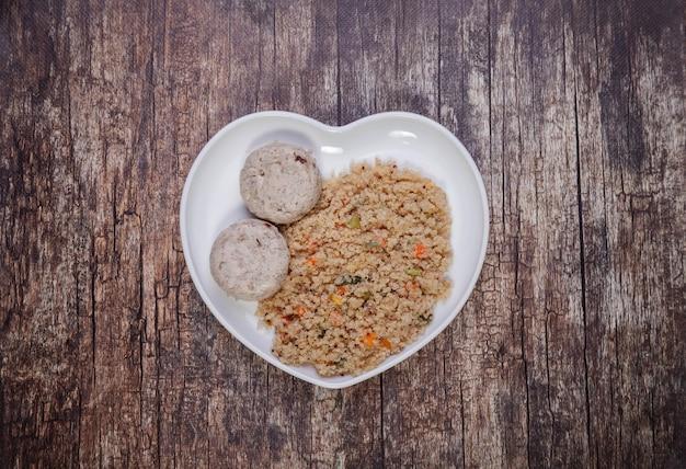 Klopsiki z fileta z kurczaka z przyozdobionym quinoa z warzywami na drewnianym tle. tradycyjne zdrowie żywności w białym talerzu w formie serca z kotletami. pyszna zdrowa dieta. skopiuj miejsce