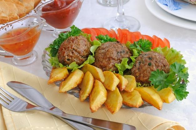 Klopsiki z zieleniną na liściach sałat z ziemniakami i pomidorami