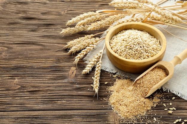 Kłosy otrębów, zbóż i pszenicy na brązowym drewnianym stole