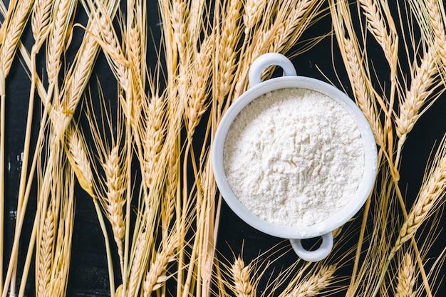 Kłosy pszenicy i mąka na czarno