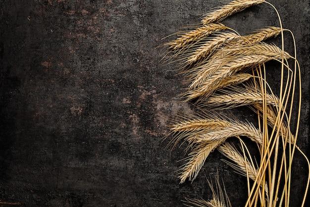 Kłosy pszenicy i żyta leżące na starym rustykalnym stylu