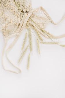 Kłosy żyta w worek strunowy na białym tle na białej powierzchni