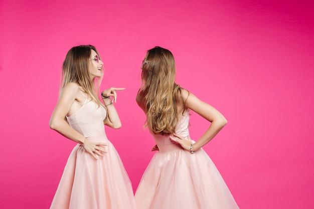 Kłótnia dwóch sióstr w różowych sukienkach.
