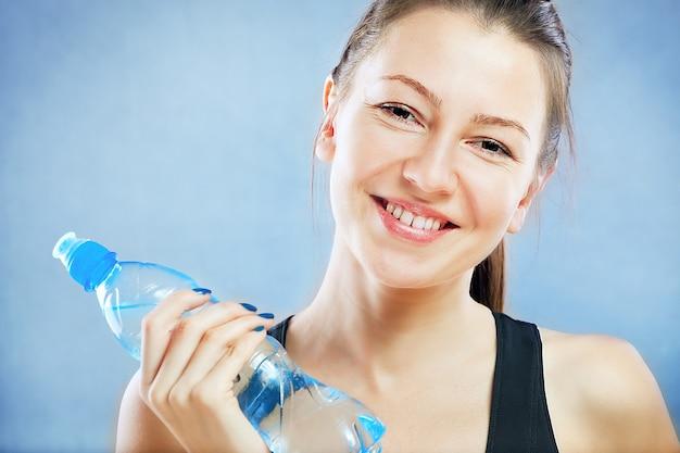 Klub fitness młoda dziewczyna z butelką wody