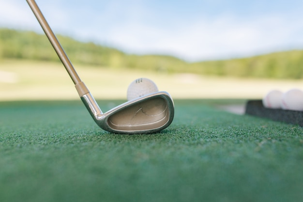 Klub golfowy i piłka w trawie. widok od tyłu
