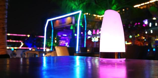 Klub nocny, bar, kawiarnia. tropikalny klubowy bar na plaży w nocy z fioletowymi, zielonymi i niebieskimi światłami