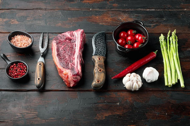 Klubowy surowy stek z ziołami i solą przygotowany do gotowania, na ciemnym drewnianym stole, z miejscem na kopię
