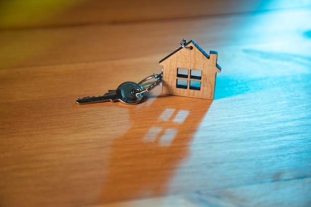 Klucz do domu na breloczku w kształcie domu na drewnianym tle