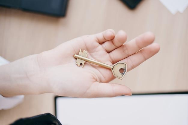 Klucz do domu w ręku na sprzedaż agenta nieruchomości