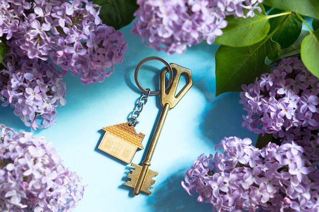 Klucz do domu z pękiem kluczy na niebieskim tle wiosny i gałęzi bzu. letni dom wakacyjny, rezerwacja domku na wsi, przeprowadzka do nowego domu, hipoteka, wynajem i zakup nieruchomości. turystyka