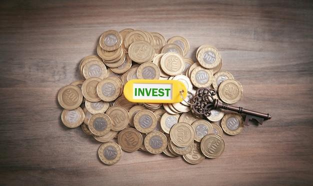 Klucz do inwestowania z monetami na drewnianym tle.