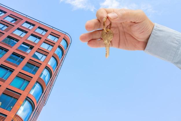 Klucz do mieszkania w męskiej dłoni. klucz mosiężny do drzwi domu. nowoczesny budynek, widok od dołu. architektura w nowoczesnym mieście. sprzedaż i wynajem nieruchomości.