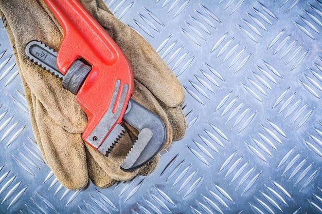 Klucz do rur ze skórzanymi rękawicami ochronnymi na konstrukcji z metalowej płyty kanałowej