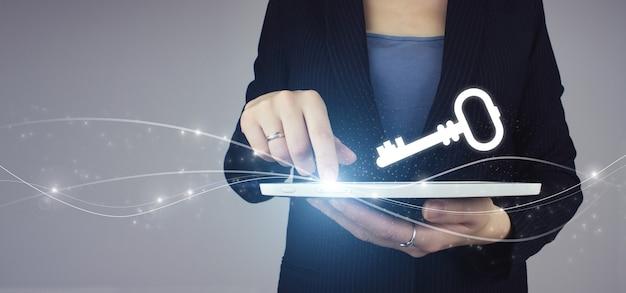 Klucz do sukcesu. biała tabletka w ręku bizneswoman z cyfrowym hologramem ikona klucza na szarym tle. koncepcja bezpieczeństwa i ochrony online.