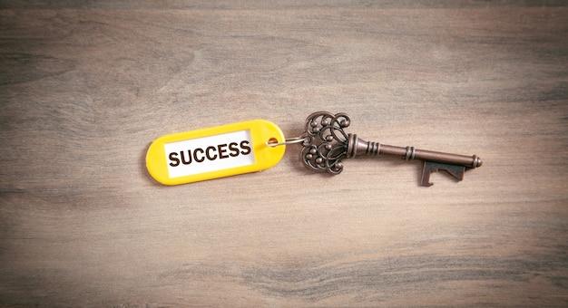 Klucz do sukcesu na drewnianym tle.