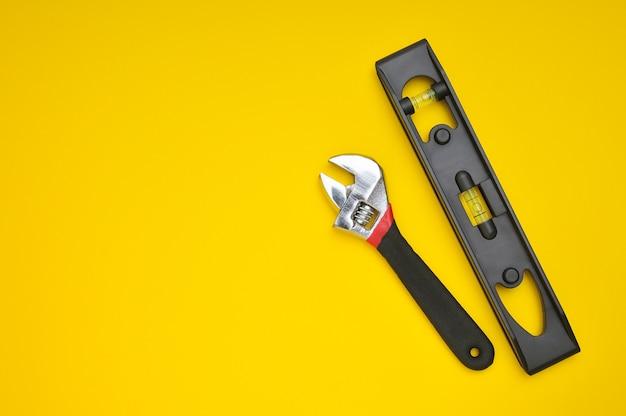 Klucz dwóch narzędzi i poziomica na żółto z miejscem na teksty