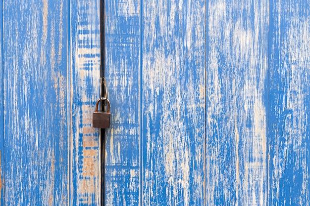 Klucz główny i stare niebieskie drzwi drewniane do zamka. padlocked na błękitnym drewnianym ściennym tle