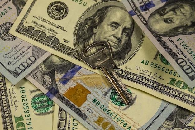 Klucz na tle amerykańskich banknotów studolarowych. koncepcja kupna lub wynajmu domu
