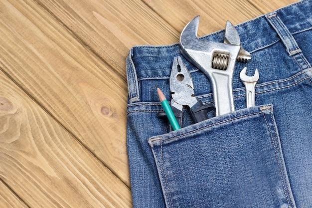 Klucz nastawny i inne narzędzia robocze w kieszeni dżinsów. narzędzia do naprawy domowej do naprawy ręcznej
