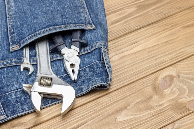 Klucz nastawny i inne narzędzia robocze w kieszeni dżinsów.
