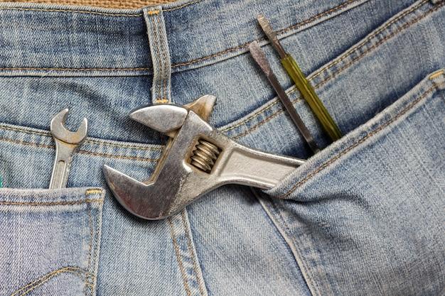 Klucz nastawny i inne narzędzia robocze w kieszeni jeansów. ścieśniać