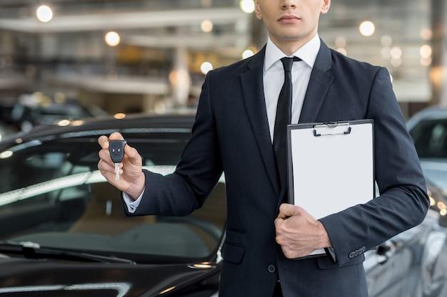 Klucz od nowego samochodu. przycięty obraz młodego sprzedawcy samochodów stojącego w salonie i trzymającego klucz