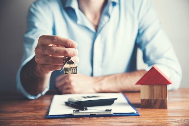 Klucz ręczny człowieka z modelem domu i dokumentem