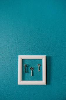 Klucz w ramce na niebieskim tle ściany. klucz nowy dom, własność domu, klucze do domu, kupno domu