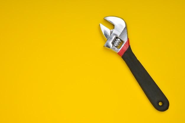 Klucz z czarnym uchwytem na żółtym tle z miejscem na tekst