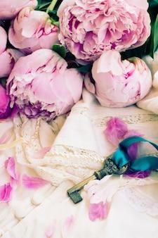 Klucz z różowymi kwiatami piwonii na koronkowym ubraniu vintage