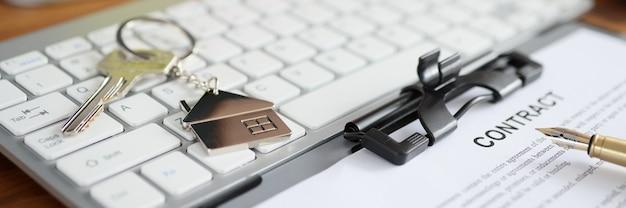 Klucze do domu i dokument z umową leżącą na zbliżenie klawiatury. koncepcja ubezpieczenia domu