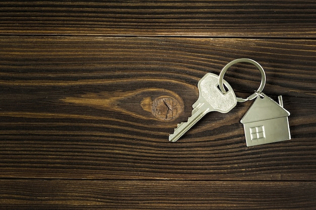 Klucze do domu leżą na ciemnym drewnianym tle