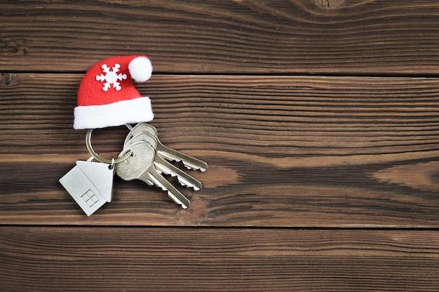Klucze do domu z czerwonym świątecznym kapeluszem na drewnianym blacie. widok z góry. koncepcja kupna nowego domu.