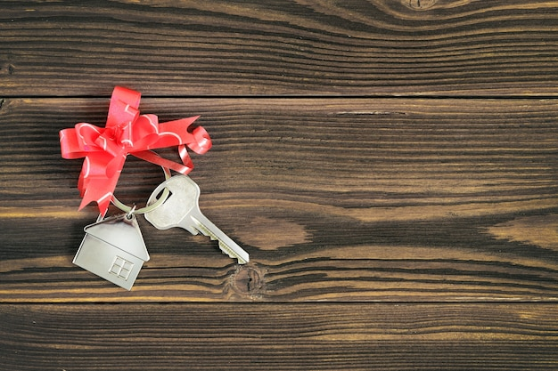 Klucze do domu z kokardą na drewnianym blacie