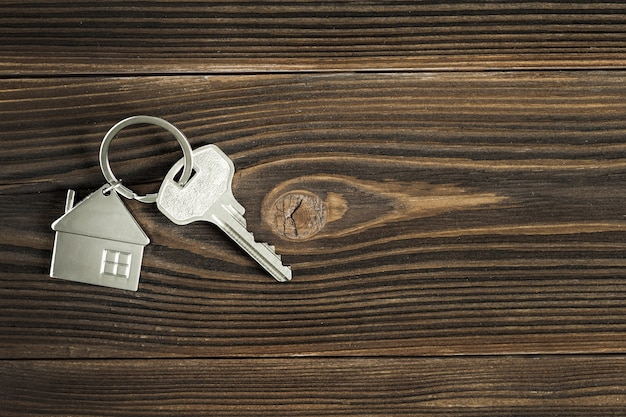 Klucze do domu znajdują się na drewnianym blacie. widok z góry. koncepcja kupna nowego domu.