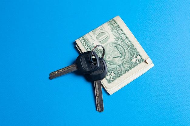 Klucze i pieniądze na niebieskim tle