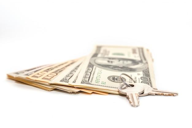 Klucze i sterta dolary odizolowywający na białym backround. sprzedaż i zakup nieruchomości.