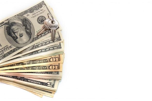 Klucze i sterta dolary odizolowywający na białym backround.