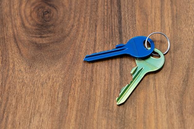 Klucze na drewnianym stole w tle wynajem sprzedam kup mieszkanie biznes nieruchomości