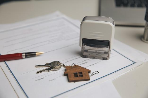 Klucze na podpisanej umowie sprzedaży domu i długopisu.