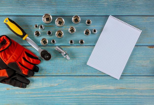 Klucze płasko-oczkowe do naprawy mechaniki samochodowej, rękawice robocze w kluczu samochodowym na drewnianym niebieskim stole