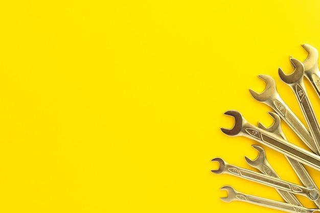 Klucze stalowe o różnych rozmiarach i średnicach na żółtym tle. zestaw kluczy chromowo-wanadowych. metalowe narzędzie do naprawy samochodów, hydrauliki, maszyn. widok płaski świeckich, poy. skopiuj miejsce.