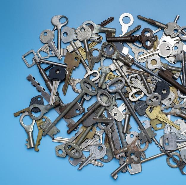 Klucze ustawione na niebieskim tle. klucze do zamków i sejfy dla ochrony mienia i domu. różne stare i nowe typy kluczy.